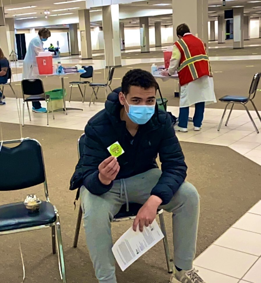 Isaiah Torok waits 15 minutes for observation following his vaccination.