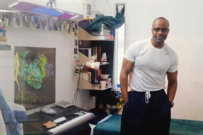 Keith LaMar stands in his prison cell in this undated photo. He has short-cropped hair and glasses and is wearing a white t-shirt and dark pants. His cell is decorated with colorful artwork and photos, and his book shelves are packed with books.