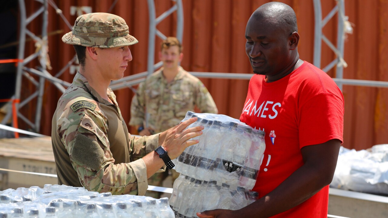 In this handout image provided by the Ministry of Defence, members of the Humanitarian and Disaster Relief (HADR) team from RFA Mounts Bay, provide aid assistance to the Islanders of Great Abaco on September 4, 2019 in Great Abaco, Bahamas. A massive rescue effort is underway after Hurricane Dorian spent more than a day inching over the Bahamas, killing at least seven as entire communities were flattened, roads washed out and hospitals and airports swamped by several feet of water, according to published reports.