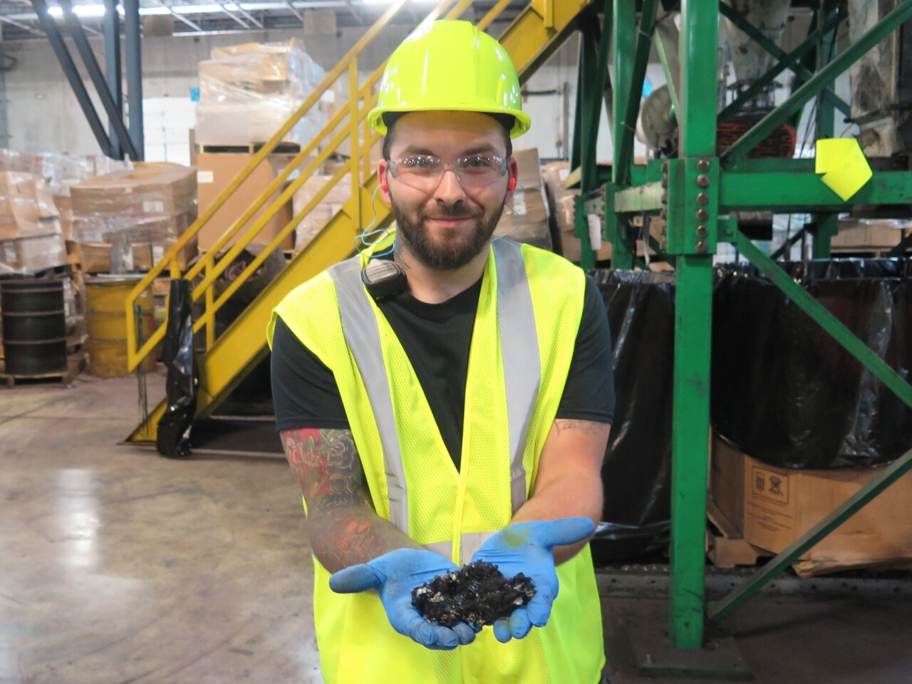 Adam Criss holds some of the toner cartridge material that Close the Loop's machines remove to be reused. The material is black and sooty looking.