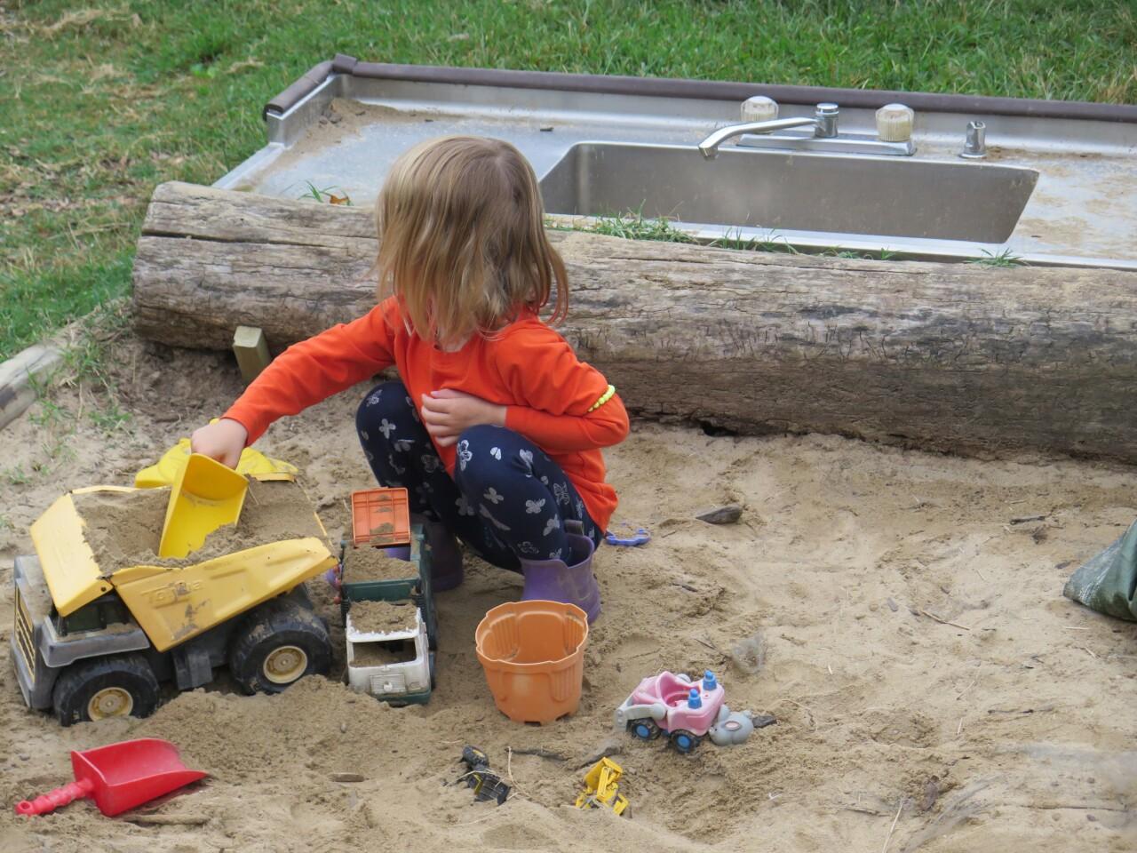 A preschool student plays in a sandbox at Shine Nurture Center on Sept. 15, 2021.