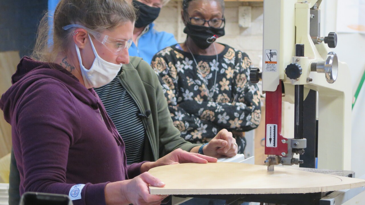 April Radcliff uses a band saw to cut a heart shape out of a piece of wood at Wave Pool's wood shop in Camp Washington. Photo taken Sept. 22, 2021.
