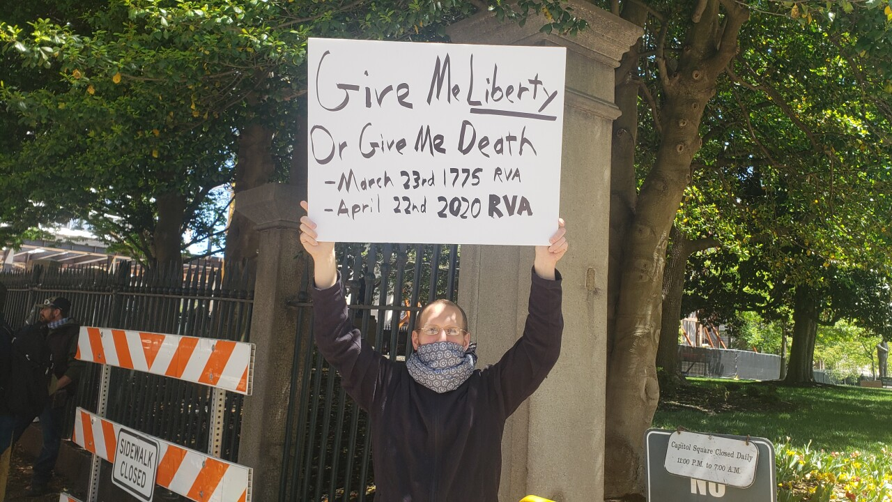 David Decker, holds a sign while he protests at the entrance to Capital Square.