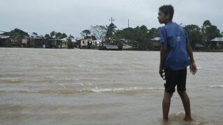 A boy looks over at the the river inundated with flood waters brought on by Hurricane Eta in Wawa, Nicaragua.
