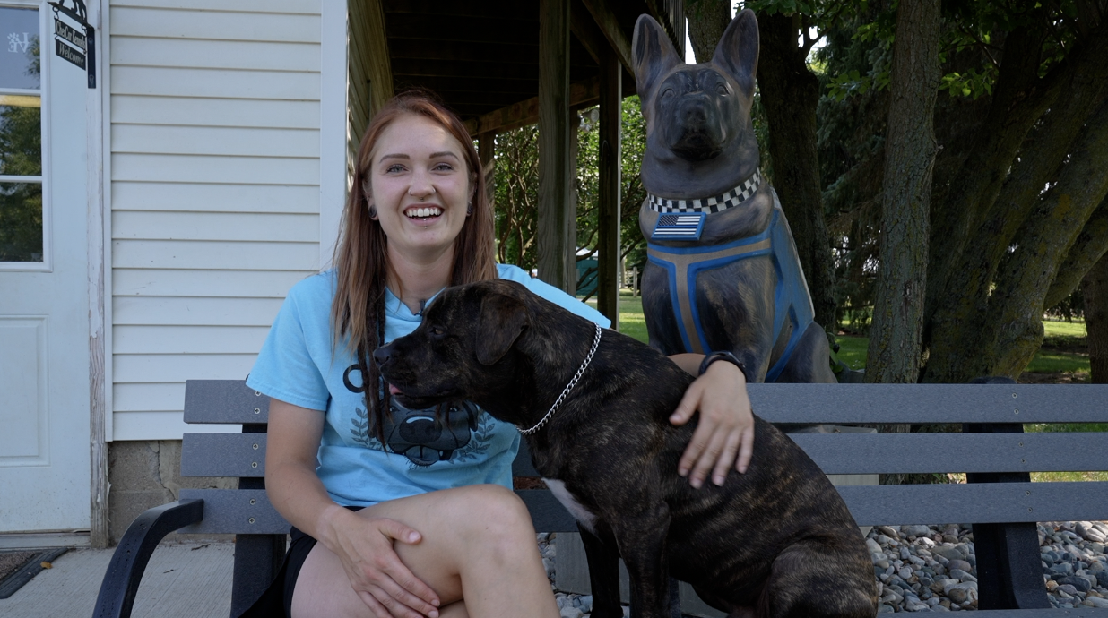Rachel Clark sitting with her dog Chewy at Cher Car Kennels