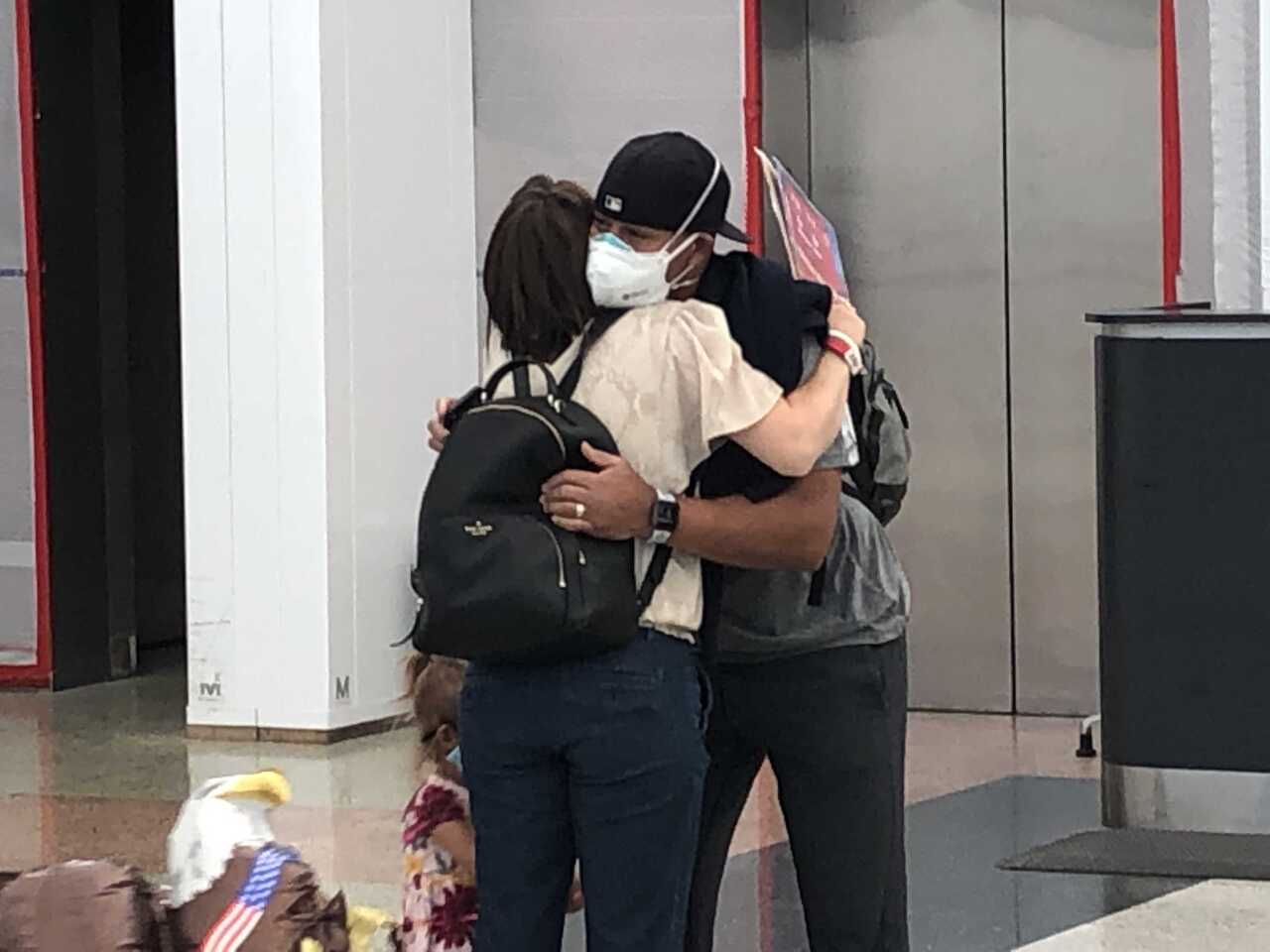 Paul and Alicia Boykin hug at DIA