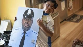 """Amethyst, Erin """"Toke"""" Tokley's five year old daughter, holds a photo of her father"""
