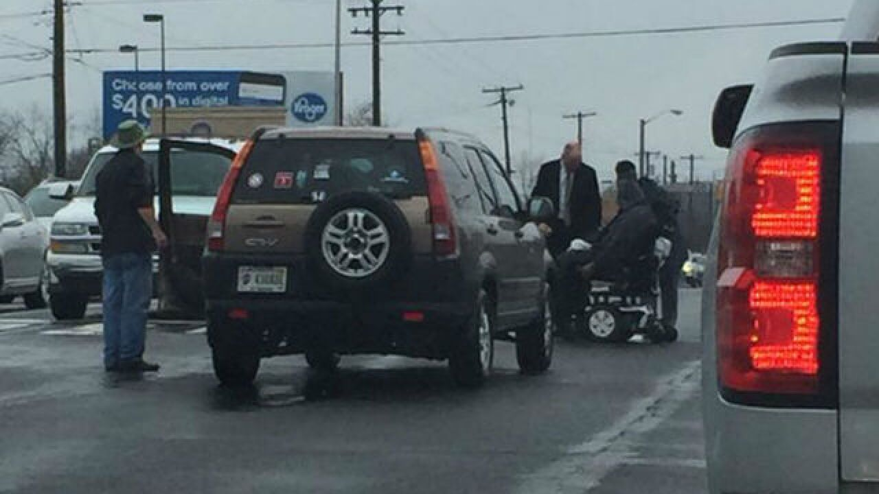People help man after wheelchair hits pothole