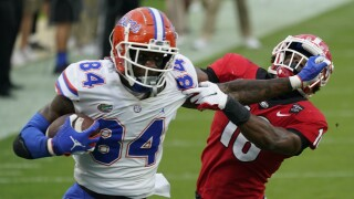 Florida Gators tight end Kyle Pitts stiff arms Georgia Bulldogs defensive back Lewis Cine in 2020