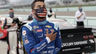 Bubba Wallace stands for the national anthem