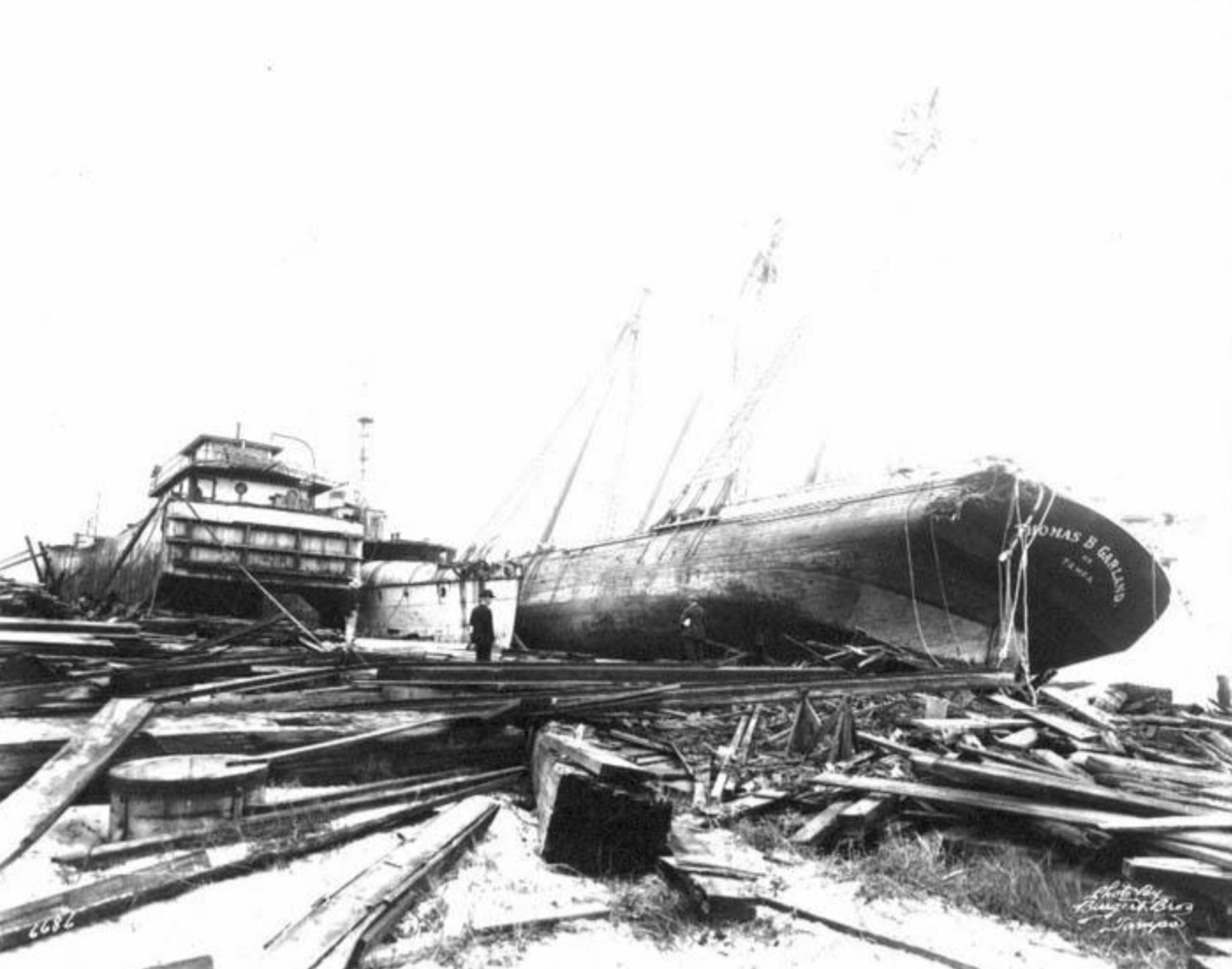 Ship, Thomas B. Garland, and barge washed ashore by hurricane, showing damage to wharf.png