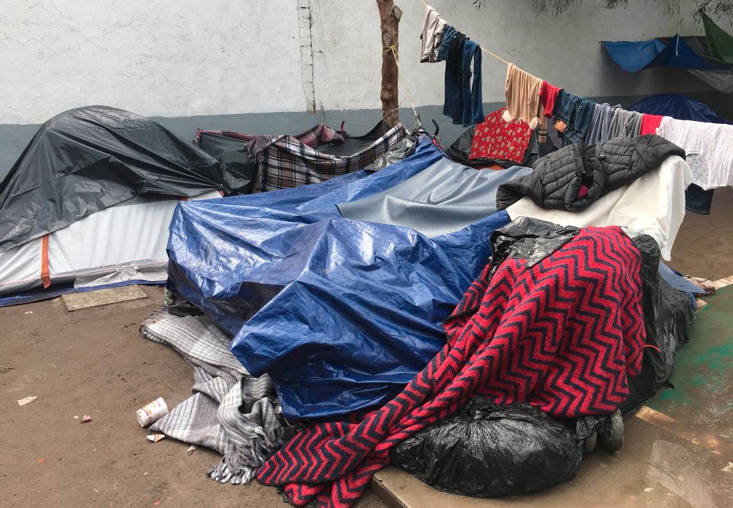 Migrants in Tijuana take shelter from the rain
