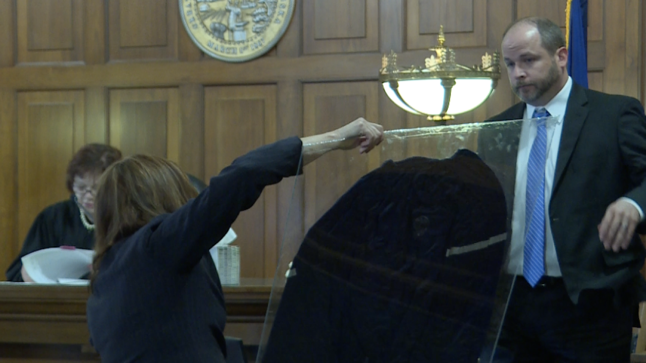 FBI agent looking at sauna outfit worn by defendants.png