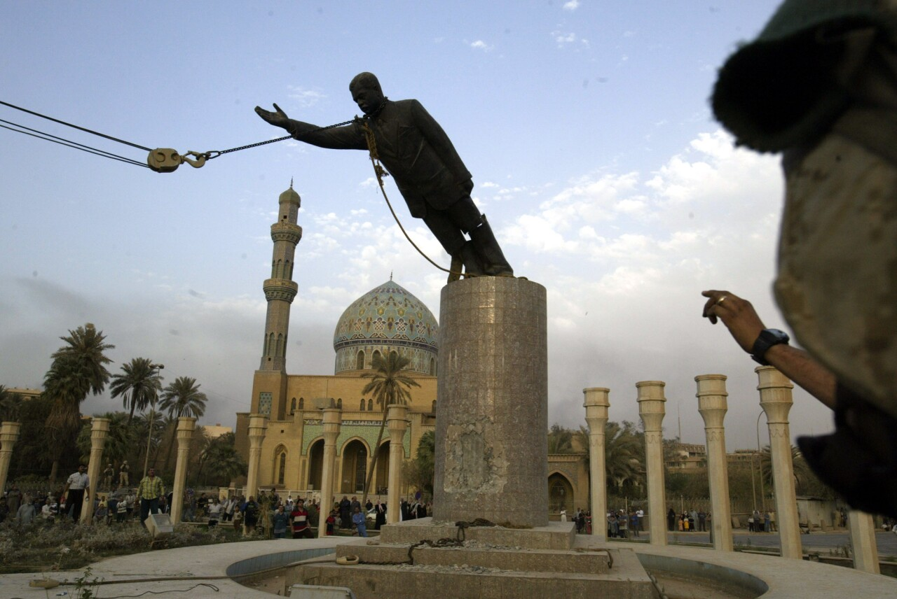 A U.S. marine watches a statue of Saddam Hussein being toppled in downtown Bagdhad Wednesday April 9, 2003. (AP Photo/Jerome Delay)
