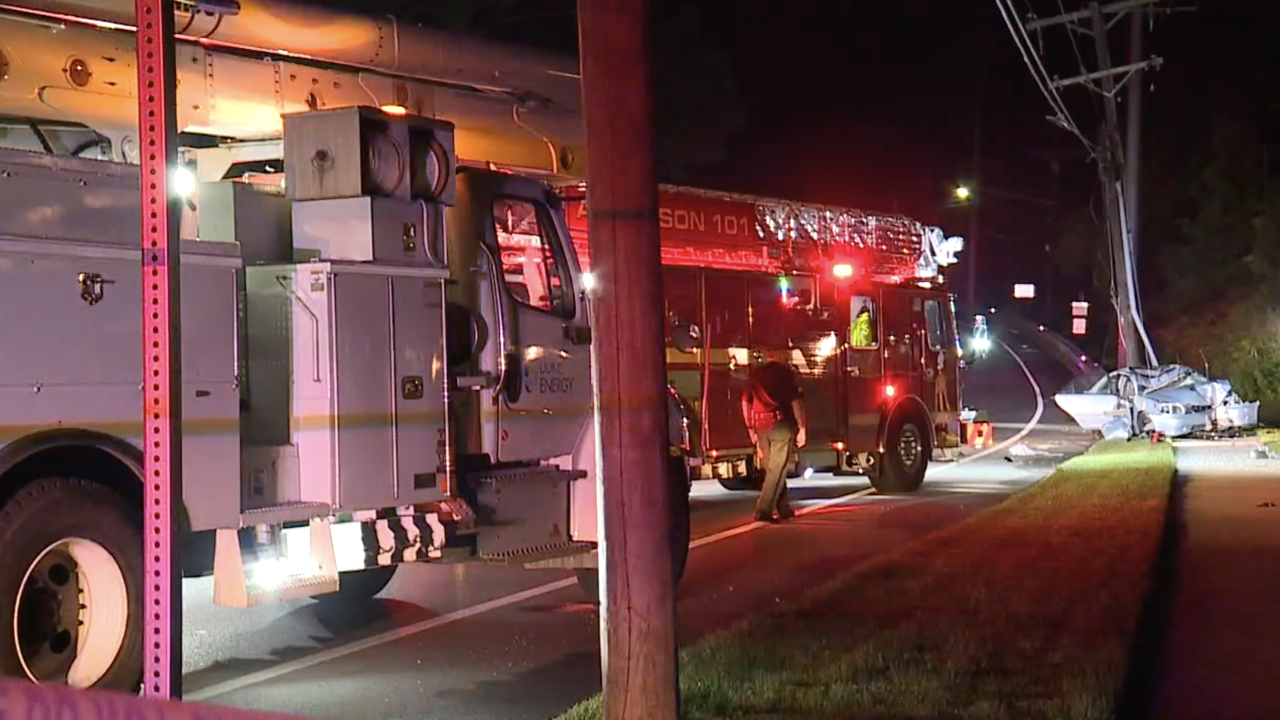 A white Duke Energy utility truck and a red Anderson Township fire engine sit at the scene of a crash in which a car smashed into a utility pole after entering a bike lane.