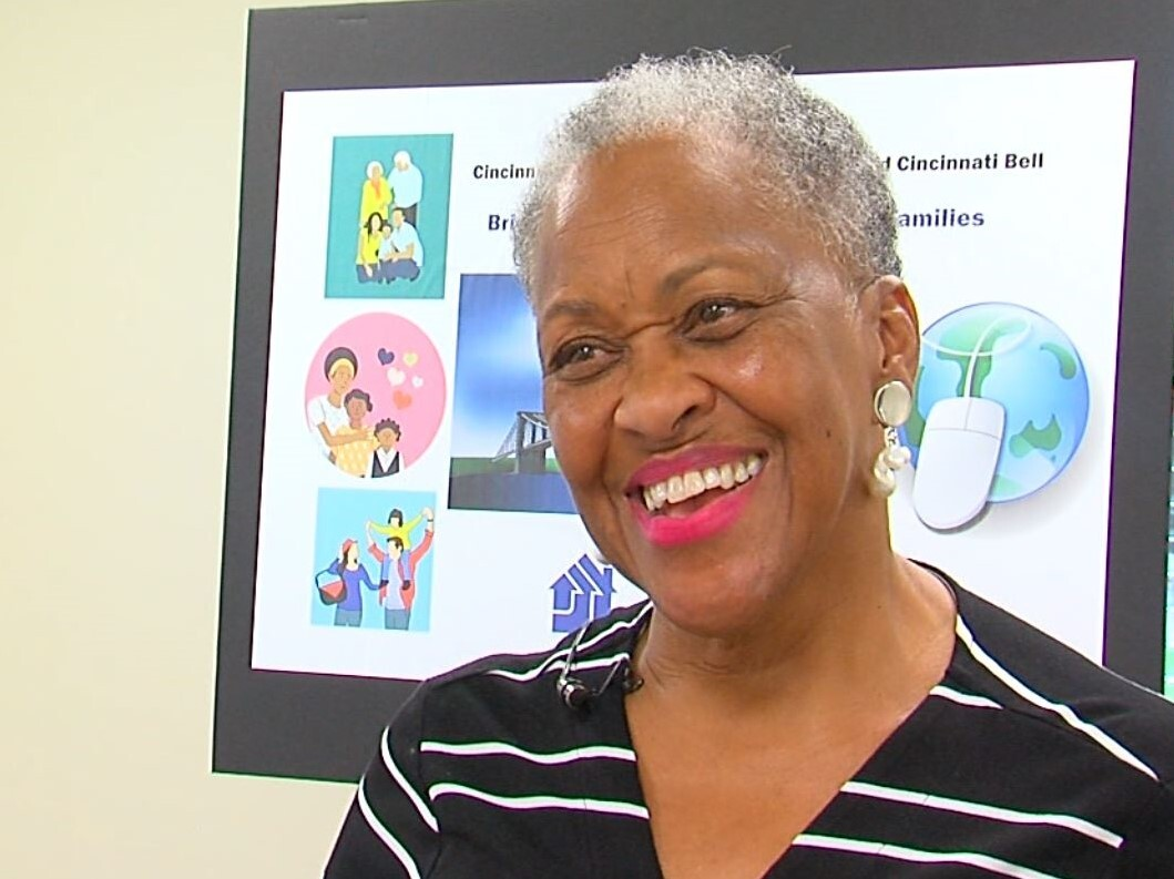 LaVerne Mitchell is smiling in this photo. She has short white and grey hair and is wearing a black dress with white stripes.