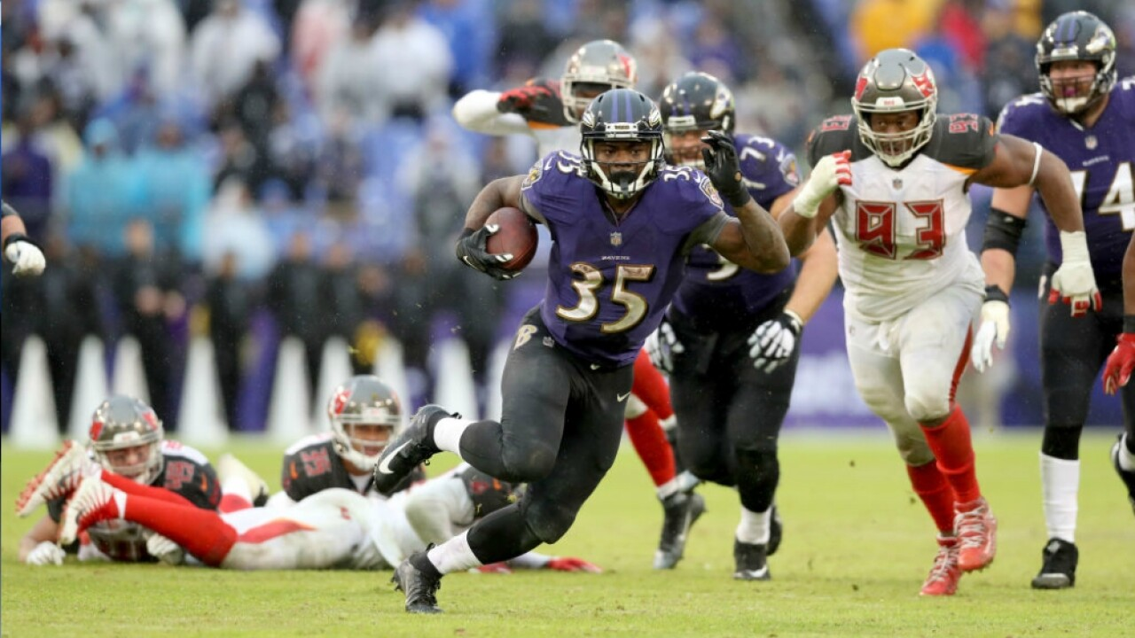 Gus Edwards runs past Buccaneers defenders