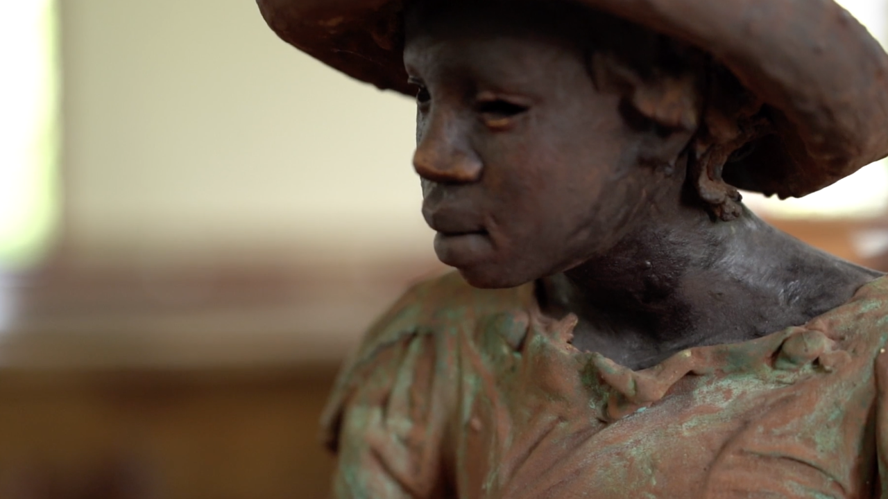 """This statue, one of the ones known as the """"Children of Whitney,"""" sits in a pew inside a church on the site of the Whitney Plantation. Their clothes are depicted as threadbare and there are no shoes on their feet."""