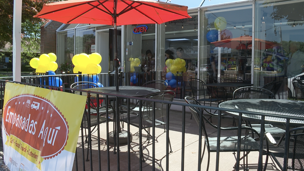 """A red umbrella covers a table on a restaurant patio, adorned with blue and yellow balloons and a red and yellow sign reading """"Empanadas Aqui."""""""