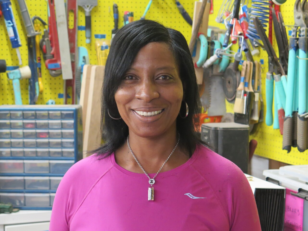 Loretta Davis is smiling in this photo. She has dark, shoulder-length hair and is wearing a bright pink shirt.