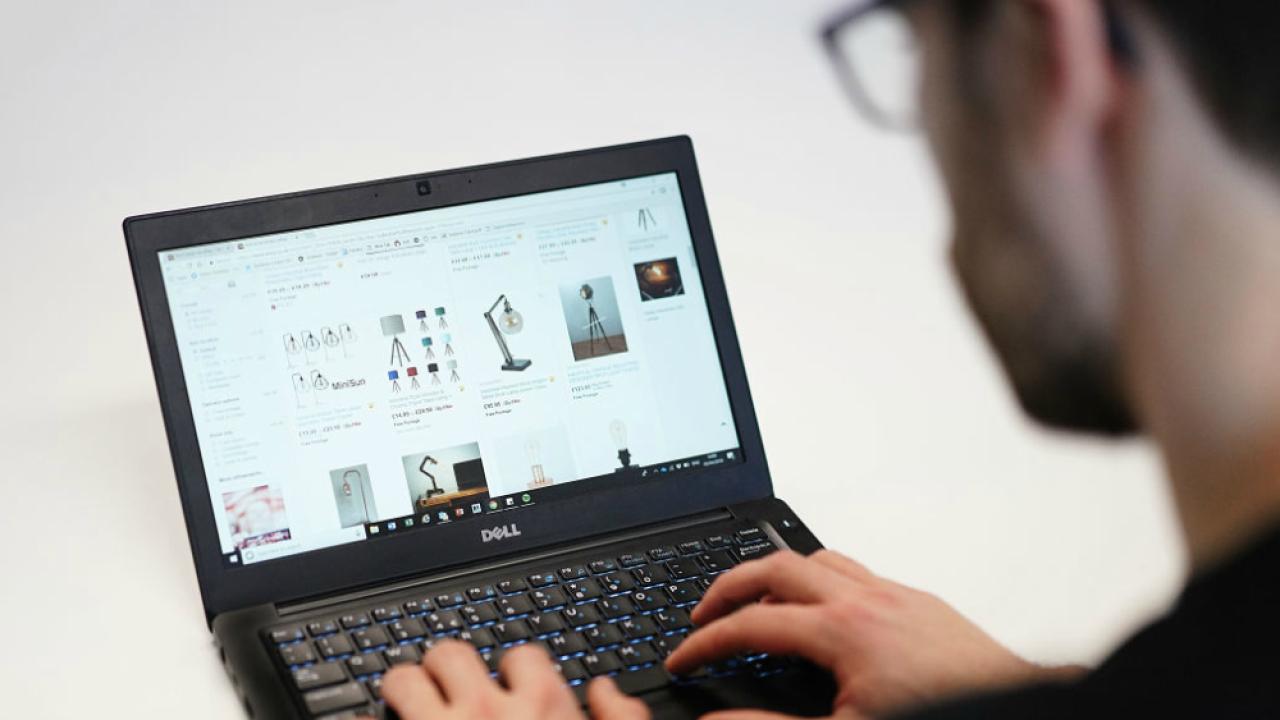 man surfing eBay on laptop
