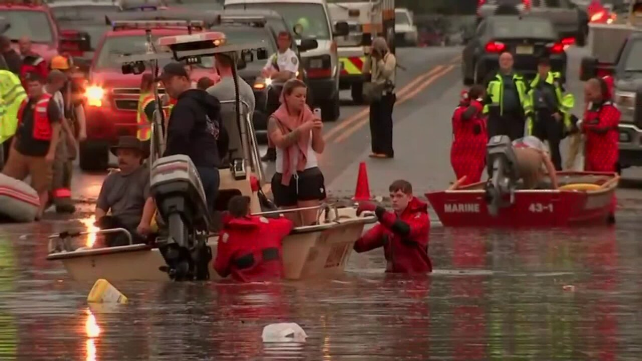 Rescuers help people from flooded cars and homes in the Philadelphia area