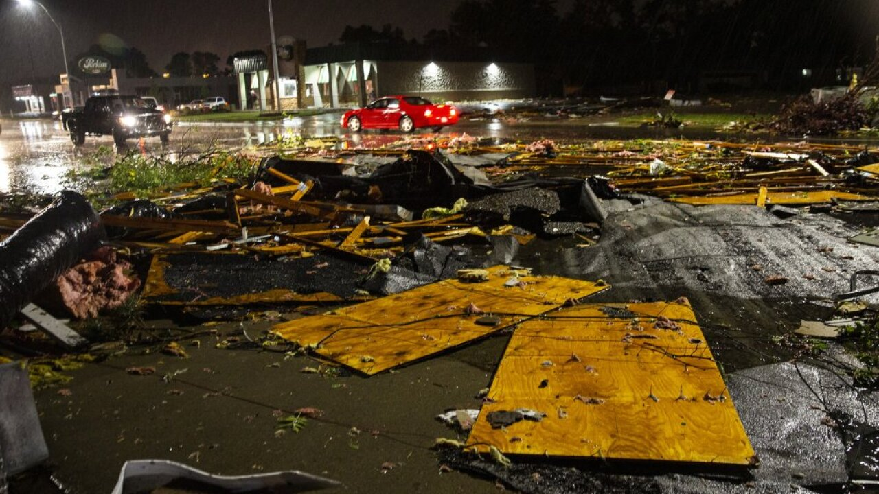 In this Tuesday, Sept. 10, 2019 photo, vehicles drive past debris littering a street after severe weather swept through the area in Sioux Falls, S.D. (Abigail Dollins/The Argus Leader via AP)
