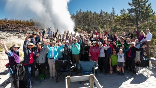 A group of people pose for a photo during the steam phase of a Steamboat Geyser eruption (courtesy NPS/Jacob W. Frank)