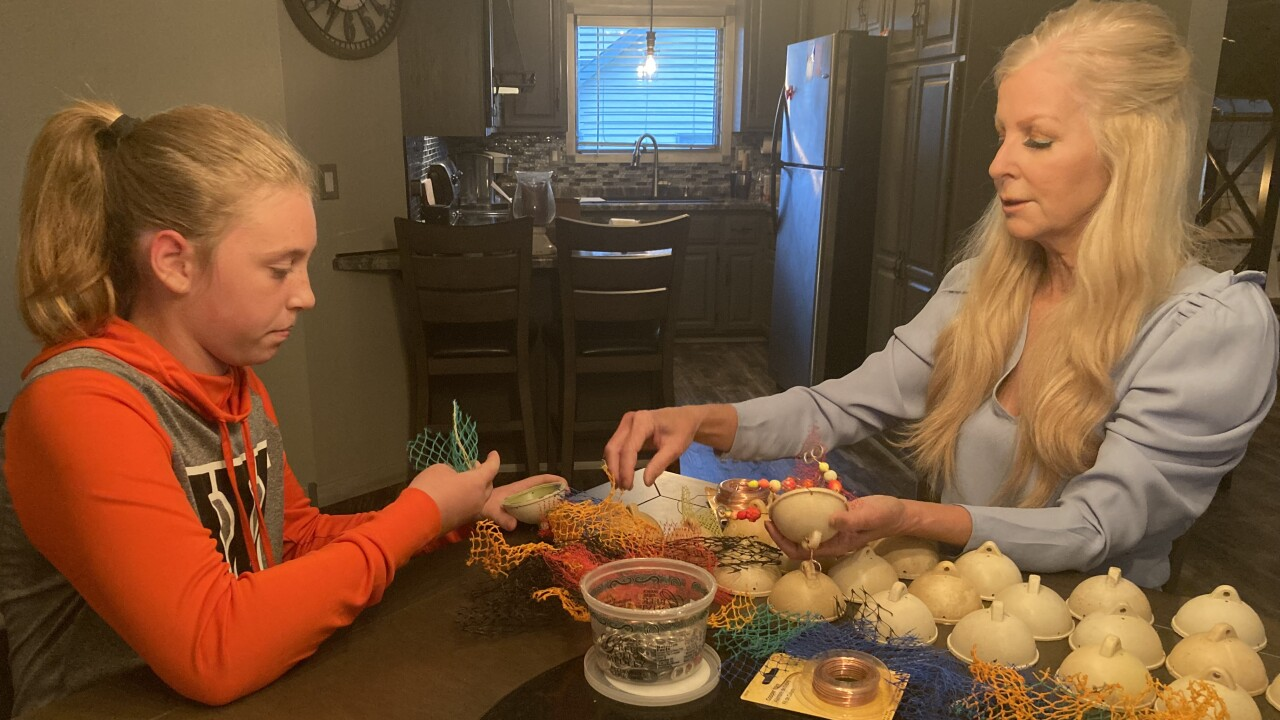 Jayne Black shows 6th grader Josie Gunn how to make a jellyfish out of sea and waterway trash.