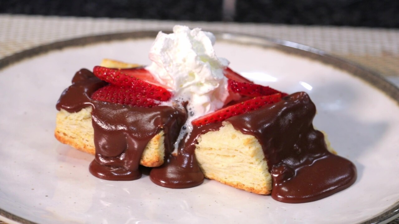 The plated biscuits covered in chocolate gravy topped with sliced strawberries and whipped cream.