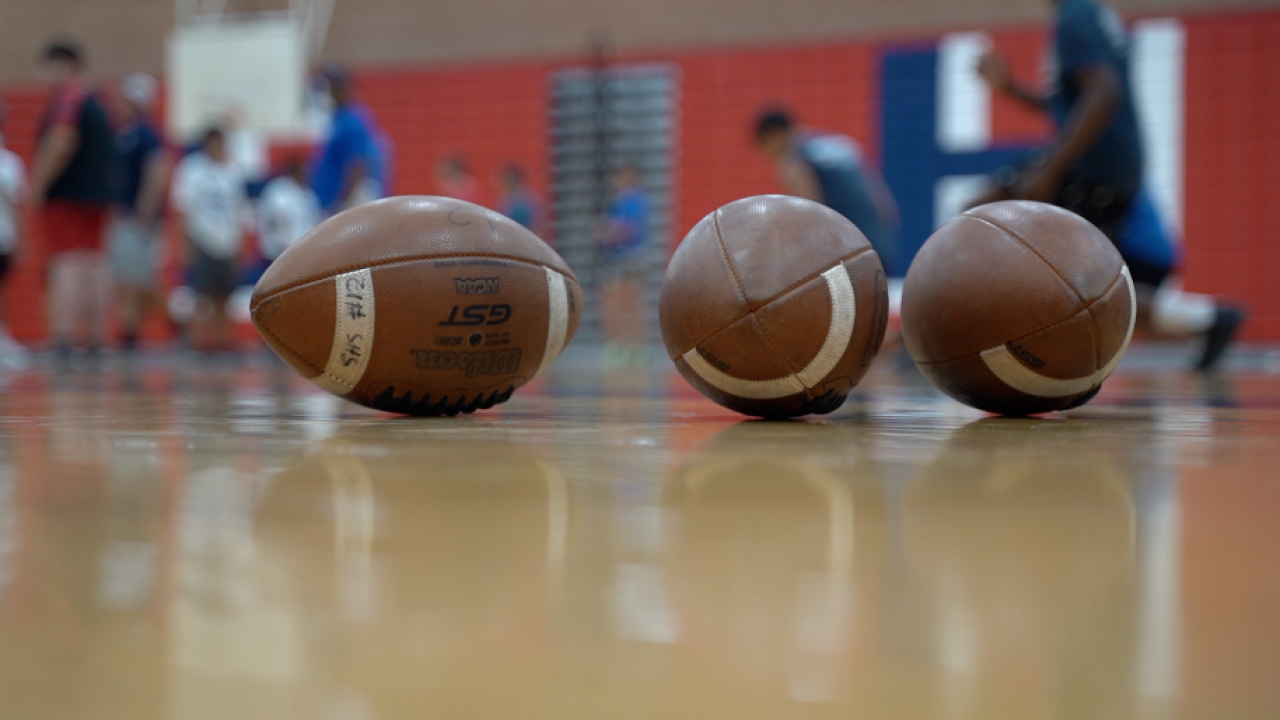 Footballs on a basketball court in Tucson, Arizona