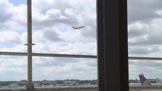 Airplane taking off seen through window at Palm Beach International Airport