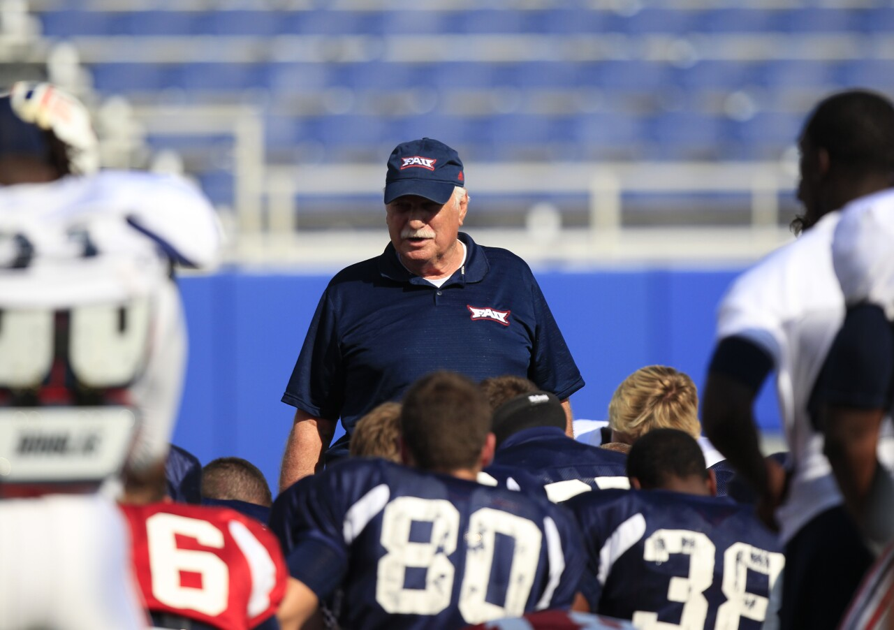 FAU Owls head coach Howard Schnellenberger talks to players on field at FAU Stadium days before home opener in 2011