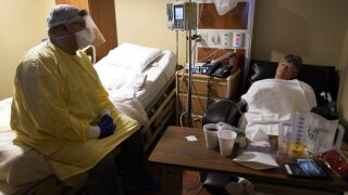 Dr. Shane Wilson, left, sits on a bed as he talks with COVID-19 patient JoBeth Harvey while performing rounds in a portion of Scotland County Hospital set up to isolate and treat COVID-19 cases. (AP Photo/Jeff Roberson)