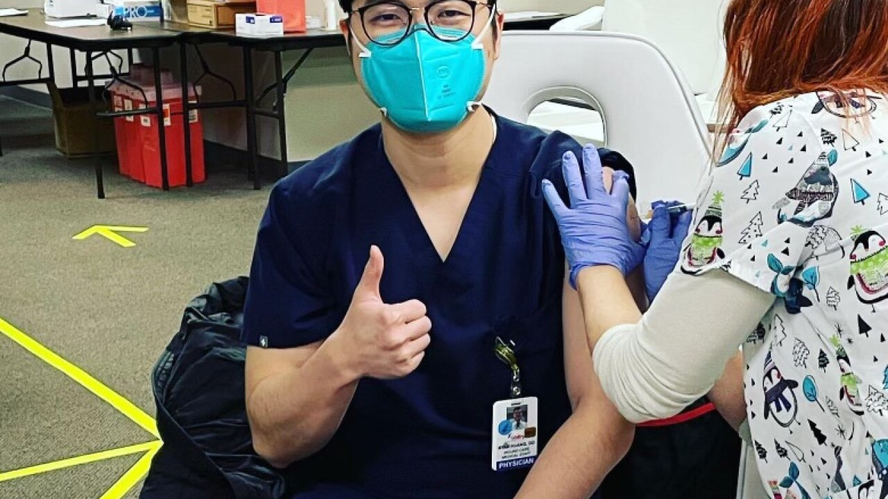 Dr. Ryan Huang poses for a picture as he receives a COVID-19 vaccination