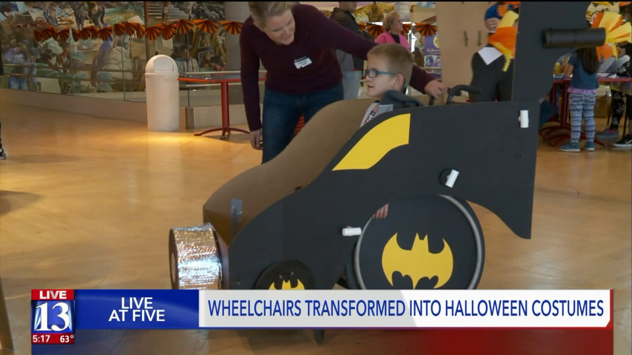 Kids in wheelchairs equipped with Halloween costumes fit for asuperhero