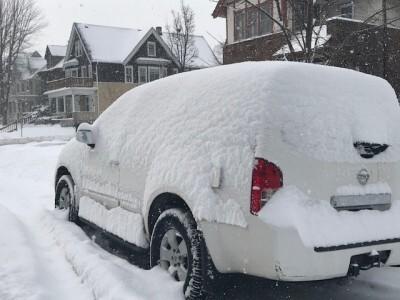 A snowy car sits on a Milwaukee street