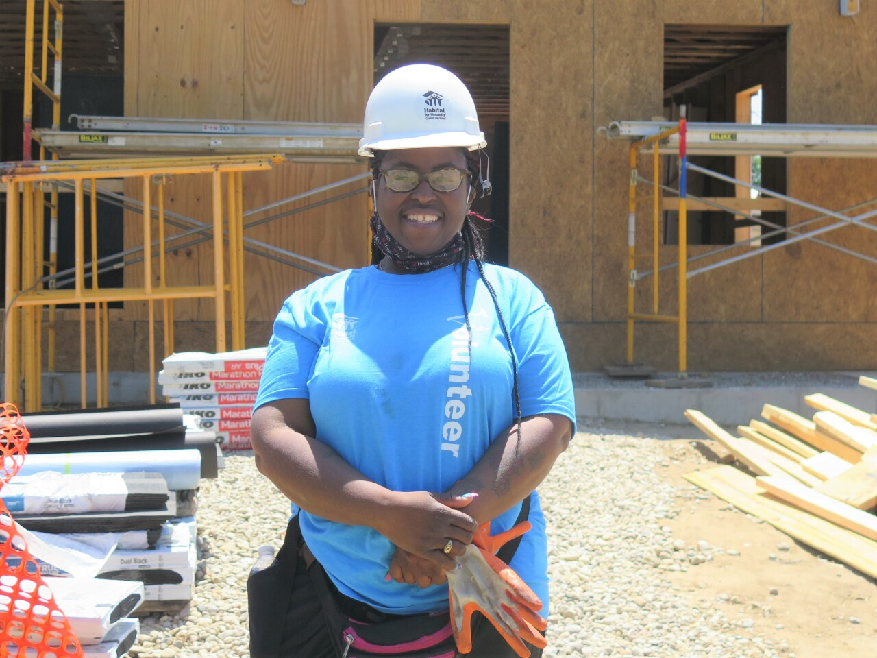 Shelisa Gilmore is smiling and wearing a white hardhat and blue t-shirt for this picture outside her Bond Hill duplex that is under construction.