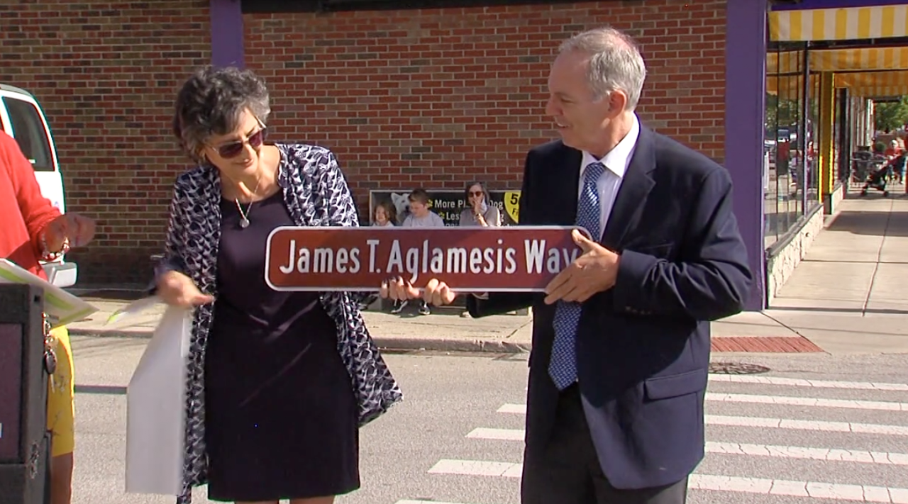 The family of James Aglamesis celebrates his honorary street name outside the family's historic ice cream shop.