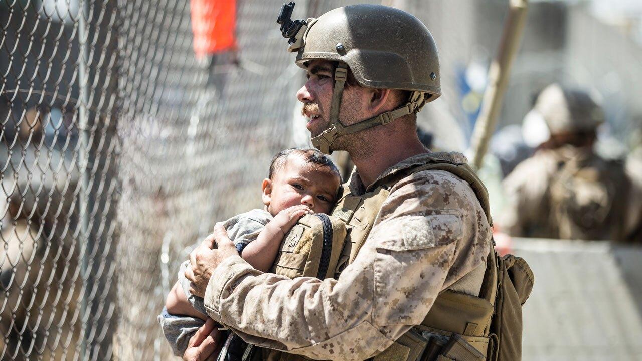 Marine holds Afghan child, Aug. 26, 2021