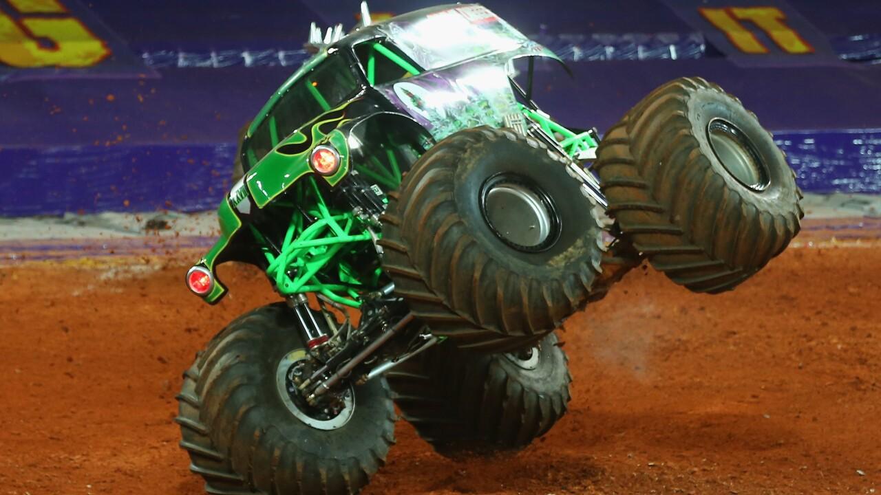 Monster truck driving on two side wheels through dirt at Monster Jam
