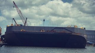 How does sinking the barge help with flooding?