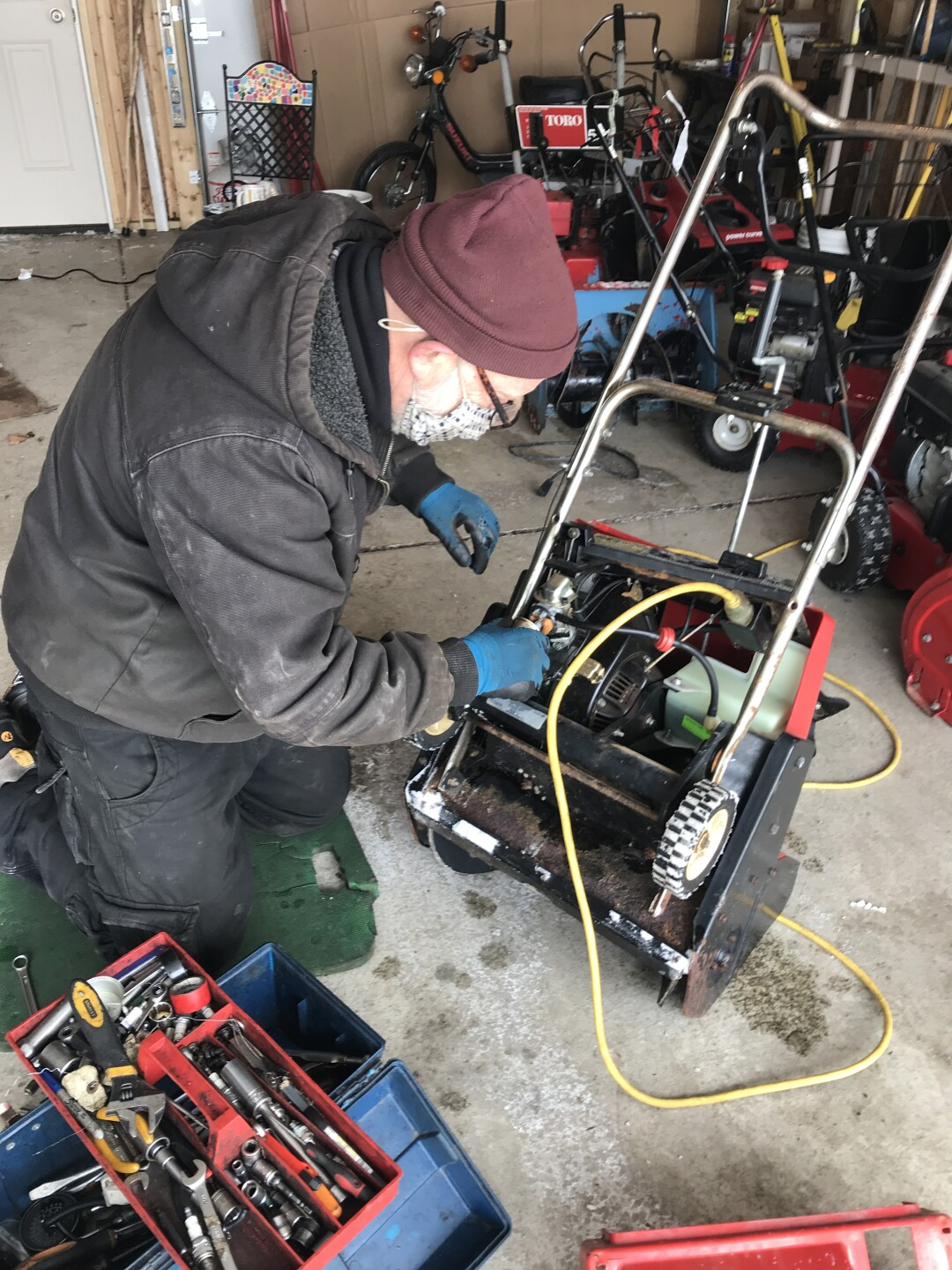 Greg Ryan works on a snowblower.