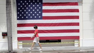 Woman wearing mask walks by American flag in Palm Beach, May 2020