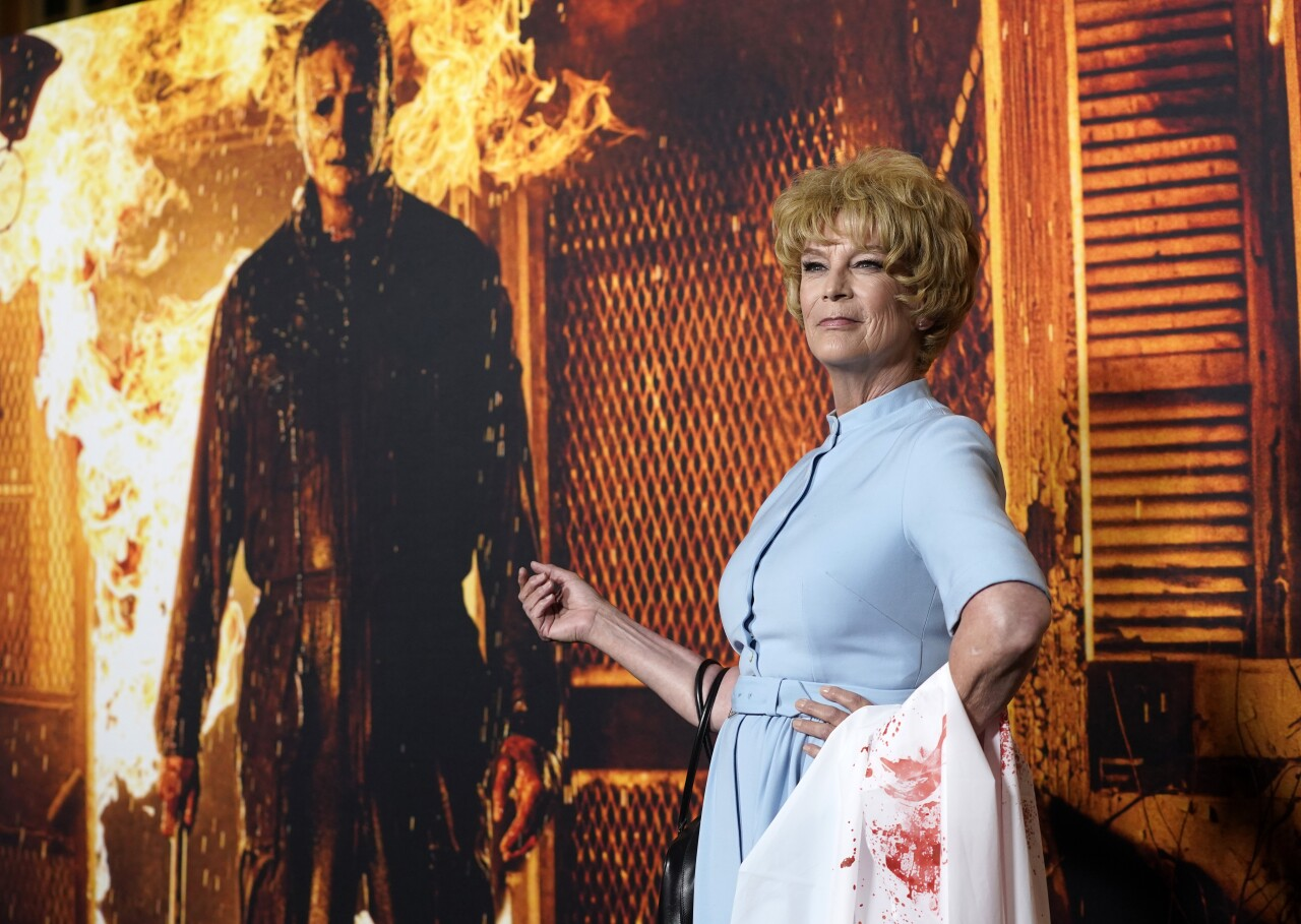 Jamie Lee Curtis dressed as Marion Crane next to photo of Michael Myers at 'Halloween Kills' premiere in 2021