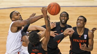 Miami Hurricanes guard Kameron McGusty and teammates battle for basketball with Clemson Tigers forward Aamir Simms in 2021 ACC Tournament