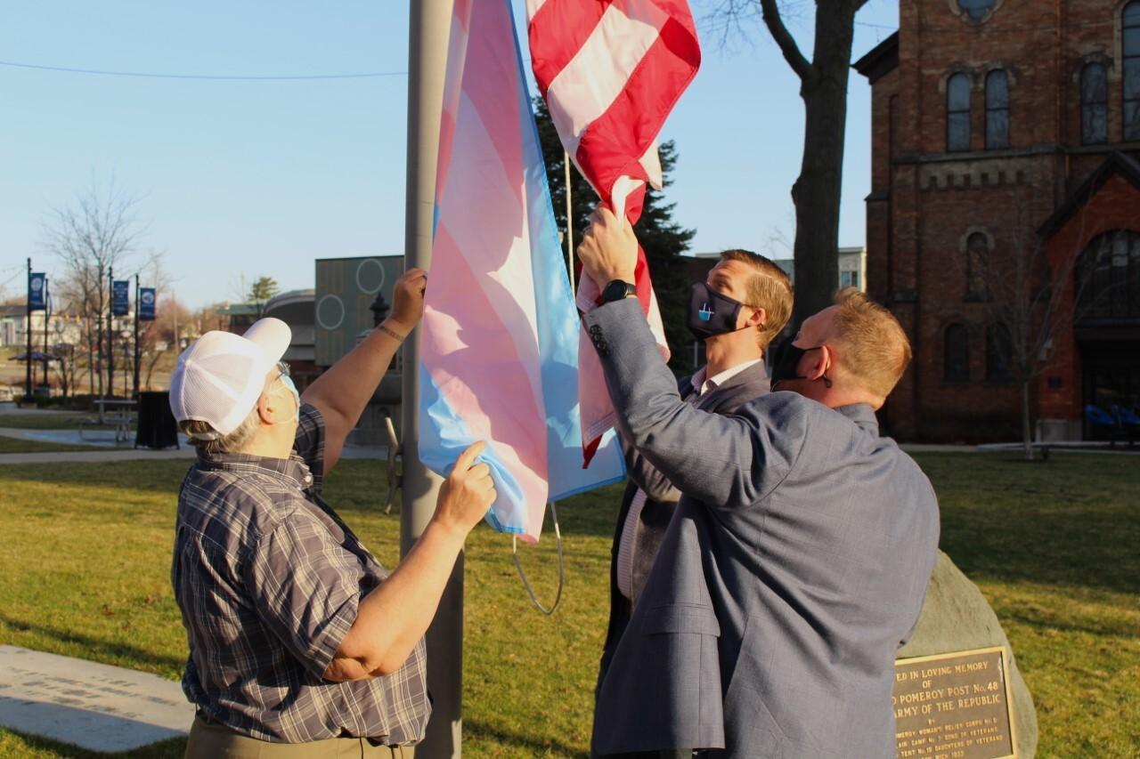 Derek Dobies raising Transgender Pride Flag