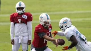 Miami Dolphins QB Ryan Fitzpatrick hands off football during training camp as Tua Tagovailoa watches, August 2020