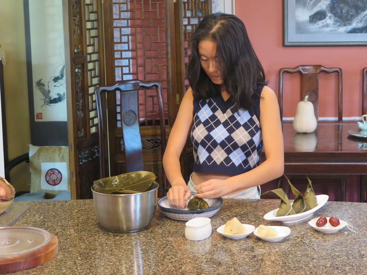 Katherine Wen ties string around a reed leaf as part of her Zongzi preparation. She is wearing a crop-top argyle sweater and has long, black hair.