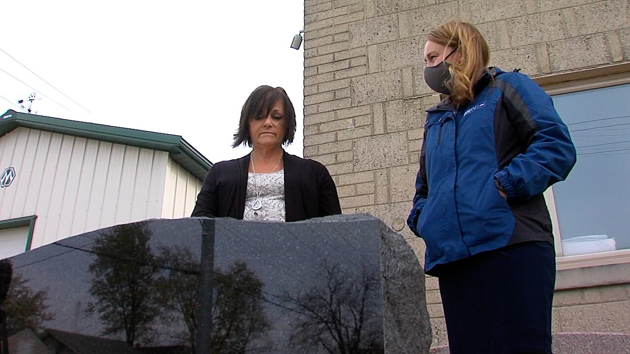 Sheila Carson looks at her mom's unfinished headstone outside Greenfield Granite